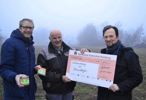 Noch etwas diesig und kahl, bald schon bunt und üppig. Christian Schäfer überreicht den Spendenscheck für das BienenBüffet an Heiner und Heinrich Wulfhorst (v.l.).