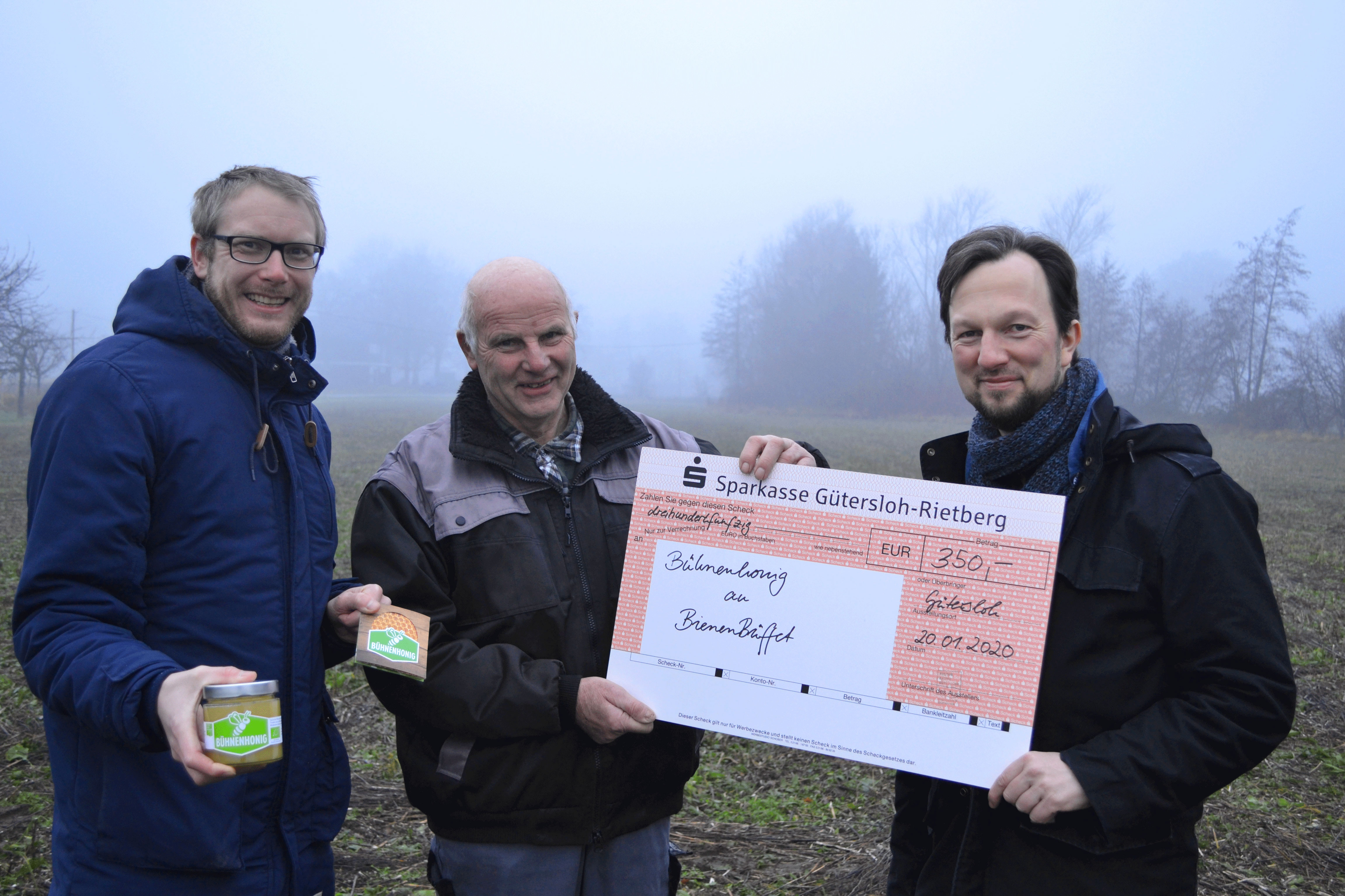 Christian Schäfer überreicht den Spendenscheck für das BienenBüffet an Heiner und Heinrich Wulfhorst